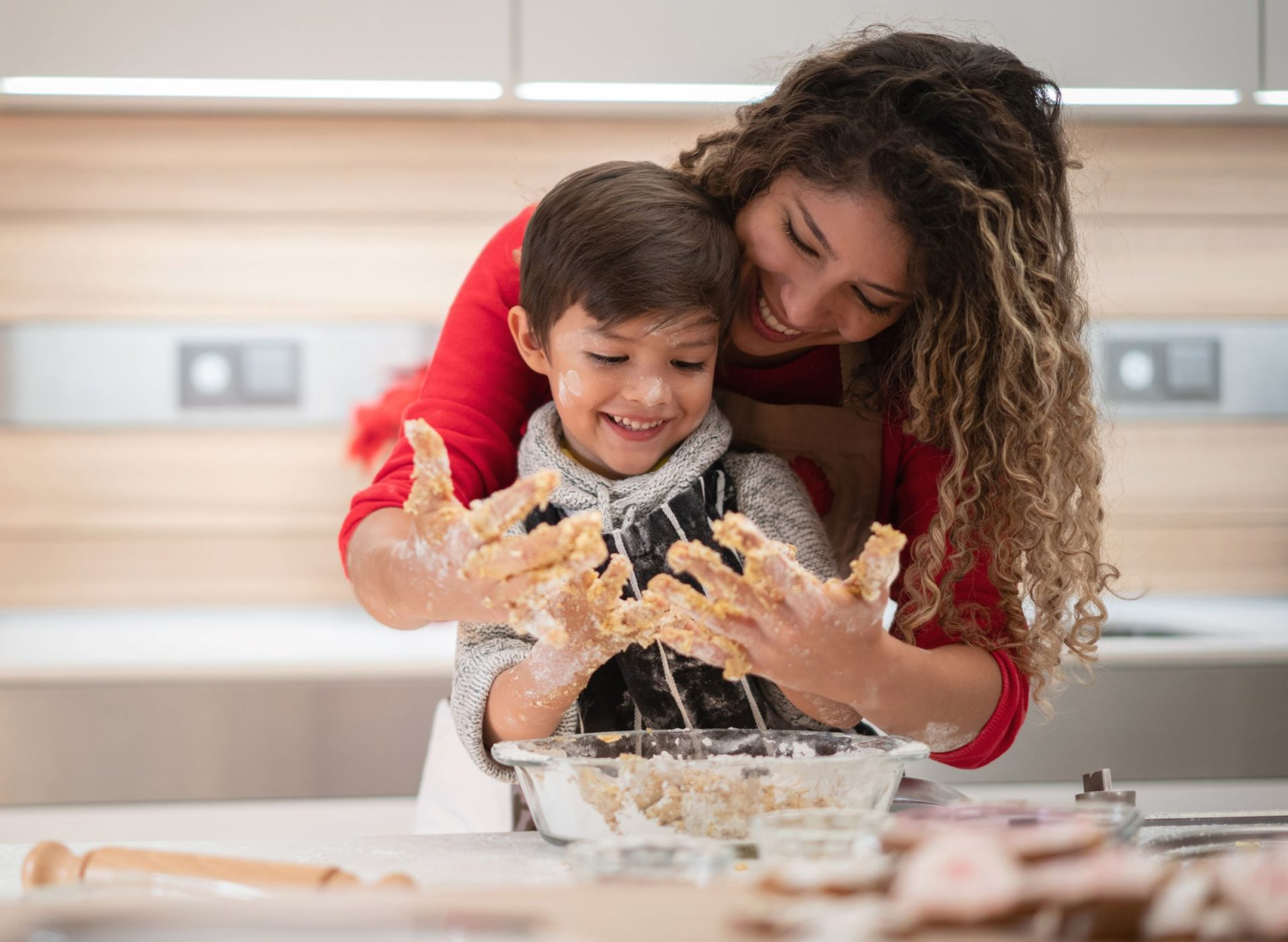Mother and child getting their hands dirty while baking